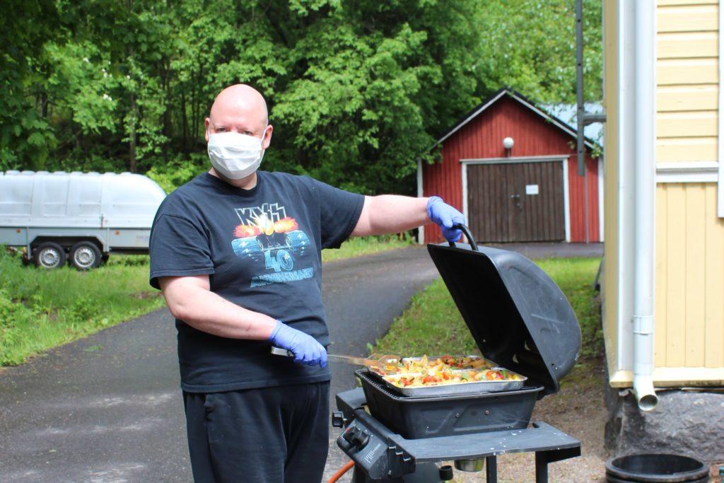 Grillausta kumihanskat käsissä ja suojamaski kasvoilla, grillaajalla päällä Kiss-yhtyeen paita, jossa liekit.