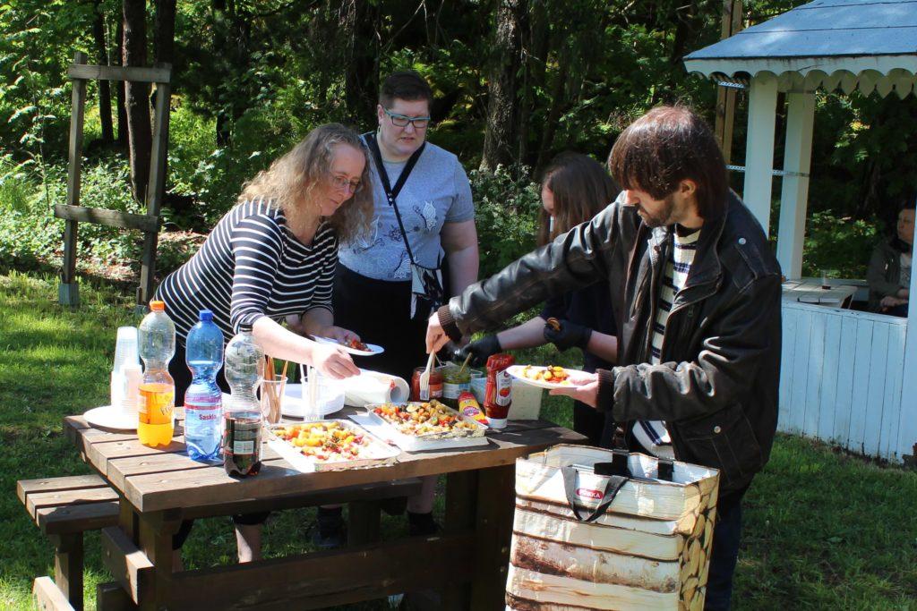 Neljä henkilöä ulkona pöydän ääressä ottamassa ruokaa.