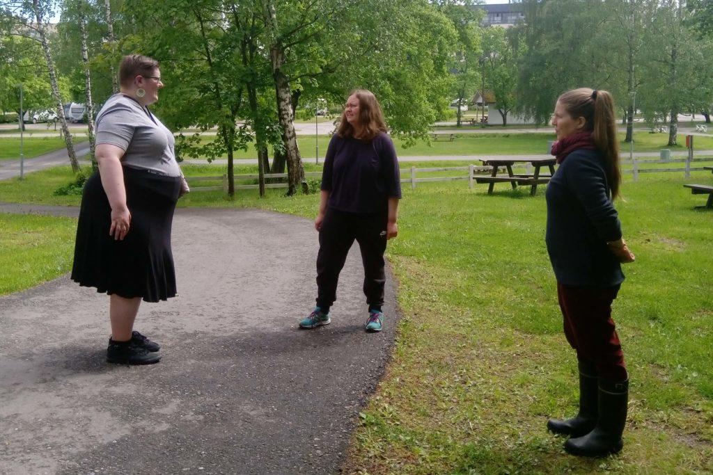 Kolme henkilöä keskustelee ulkona seisten hieman kauempana toisistaan.